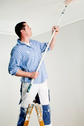 Painter on step ladder painting ceiling with a roller on a pole.